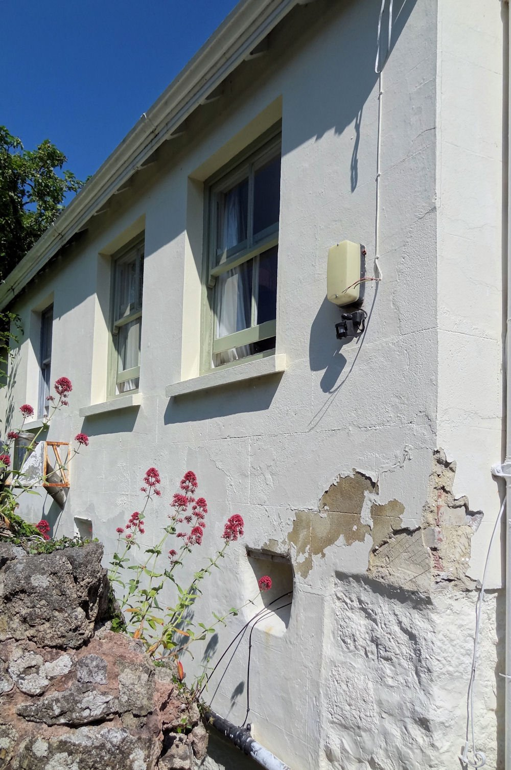 Damp cement rendered and modern painted building
