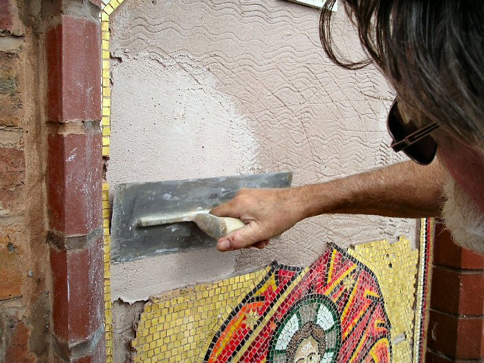 Greek church traditional mosaic using lime products. Applying the backing lime mortar mix.